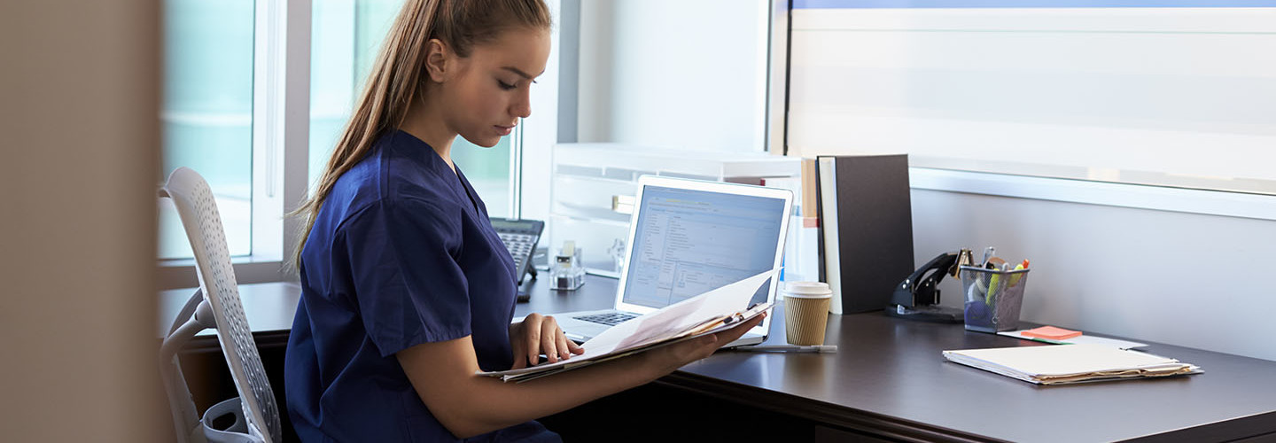 Nurse Wearing Scrubs Working At Desk In Office