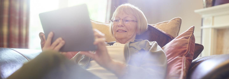 senior woman smiling as she uses her digital tablet