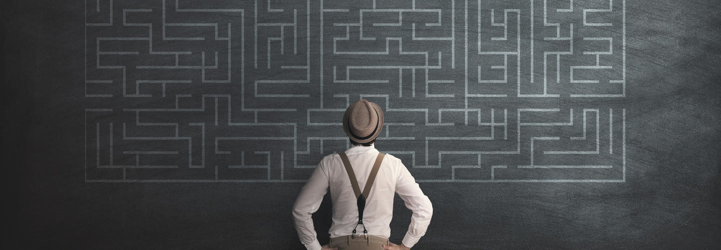 man in fedora looking at chalk maze