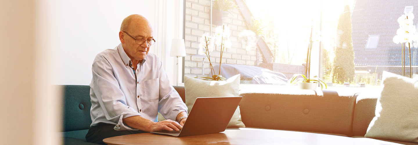 Senior man works with laptop as sun shines through windows
