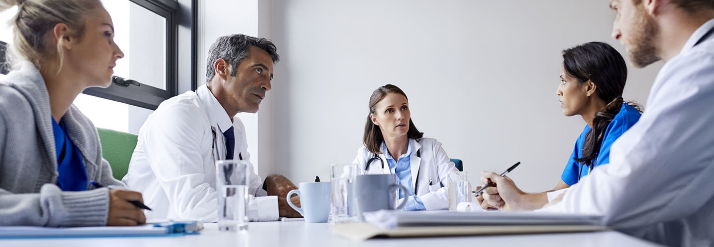 Surgeons discussing at table in board room