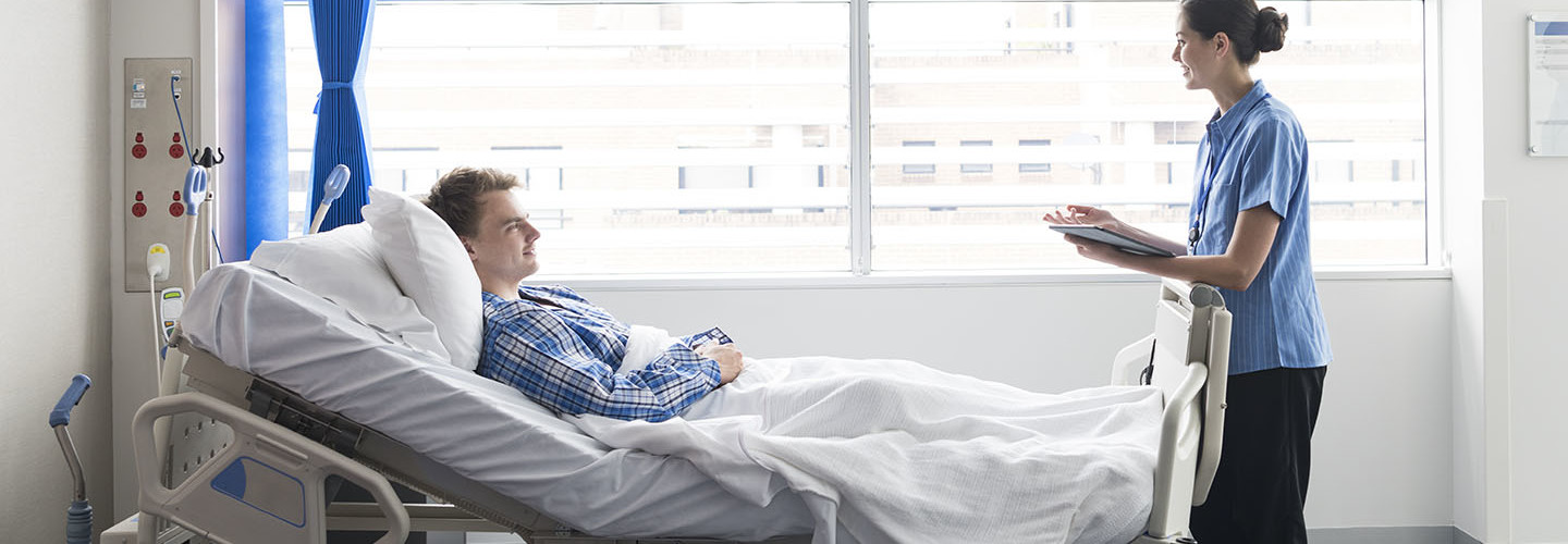 Young man lying in bed in hospital with female nurse