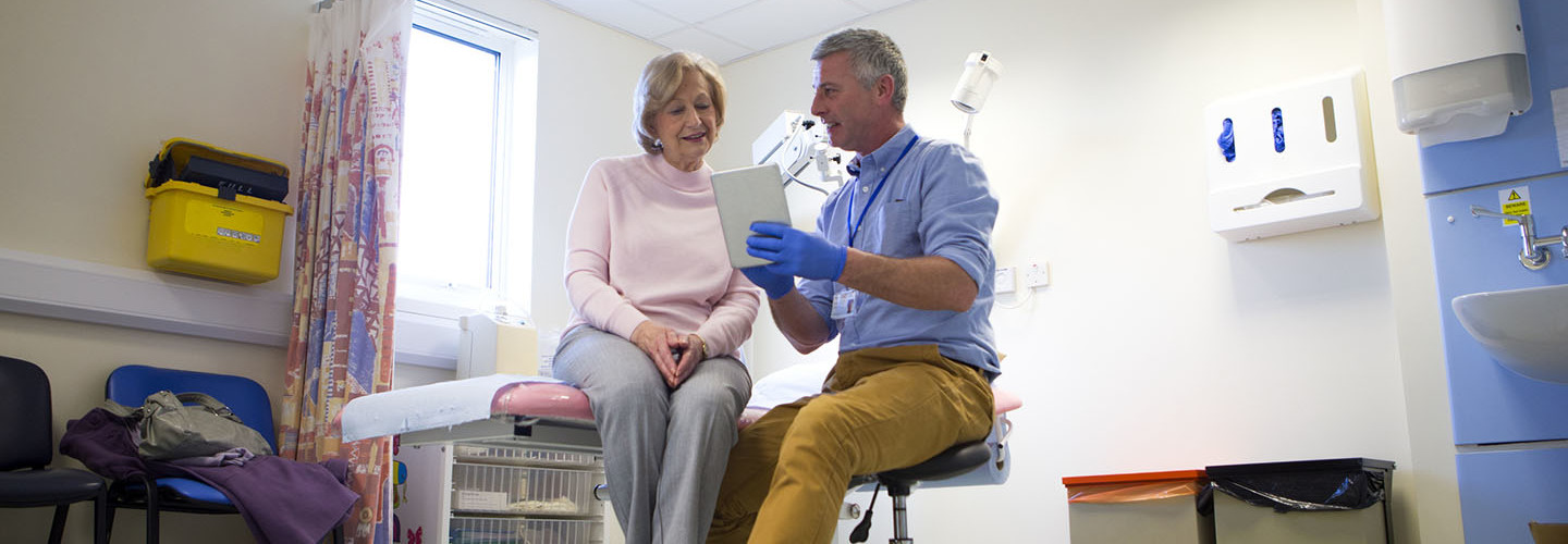 A male doctor sits beside an elderly female. They are in an examination room talking as he holds a digital tablet in one hand. The male doctor looks very happy as he smiles. View of room from a low angle