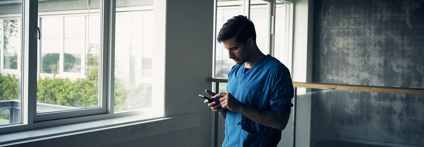 Shot of a focused young male doctor standing while being on his cellphone inside of a hospital