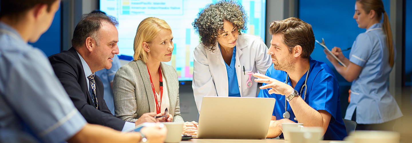 Doctors and business teams collaborating around computer