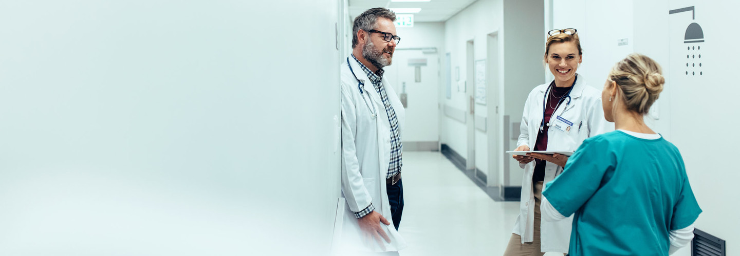 Medical team discussing in corridor at hospital. Mature doctor discussing with coworkers while standing in hospital hallway.