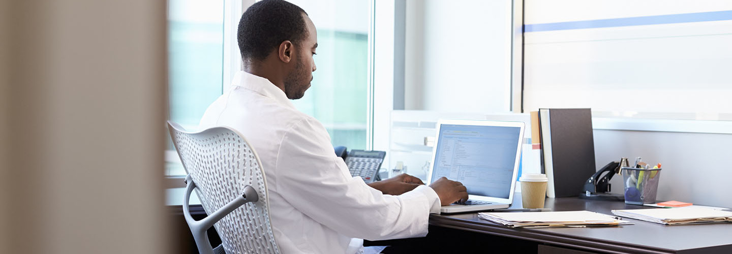 Doctor Wearing White Coat Working On Laptop In Office