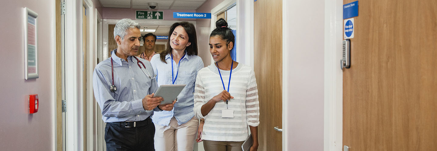 Three doctors meet in the corridor and chat along the way looking at a digital tablet