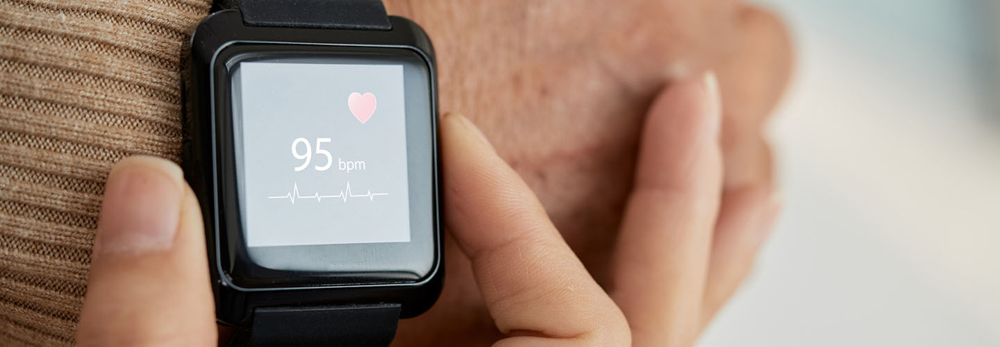Close-up shot of unrecognizable doctor checking pulse of her senior patient with help of smart watch, blurred background