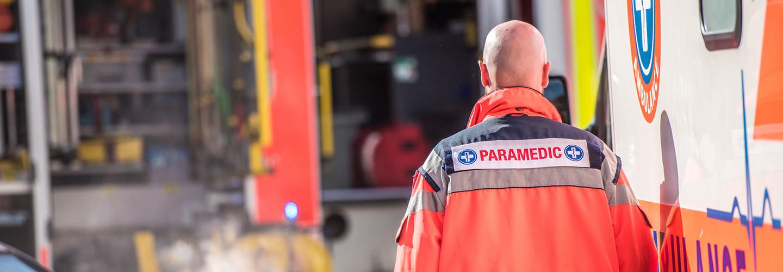 Rear view of male paramedic walking outside ambulance.