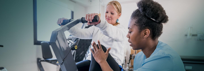 Nurse helping woman on rehab bike