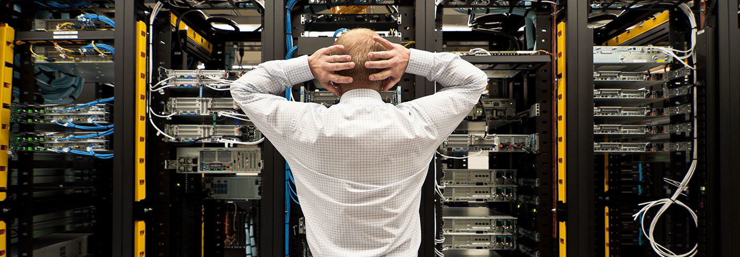 A man looking at a row of servers.