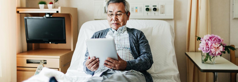 Man Reading on iPad in Hospital Room