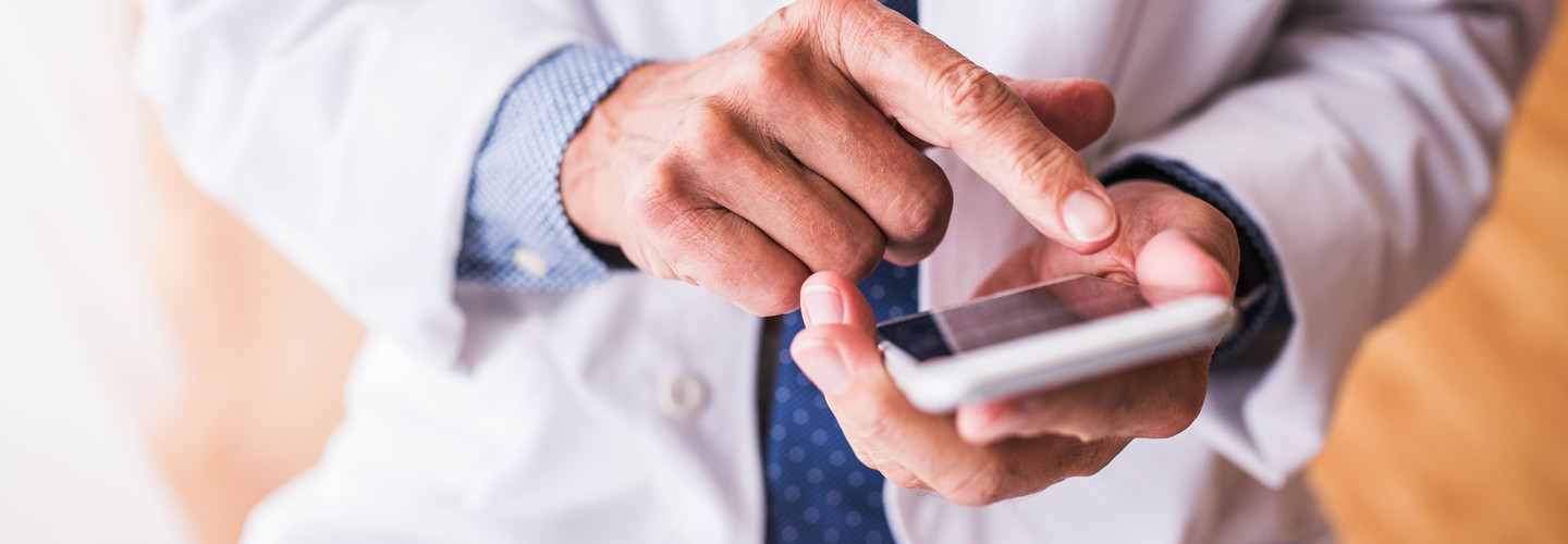 Doctor uses phone to interact with patient.
