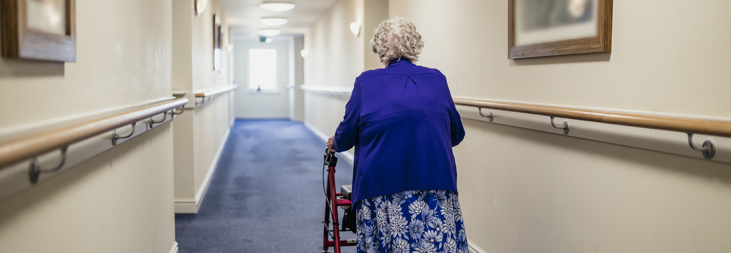 Senior walking in nursing home.