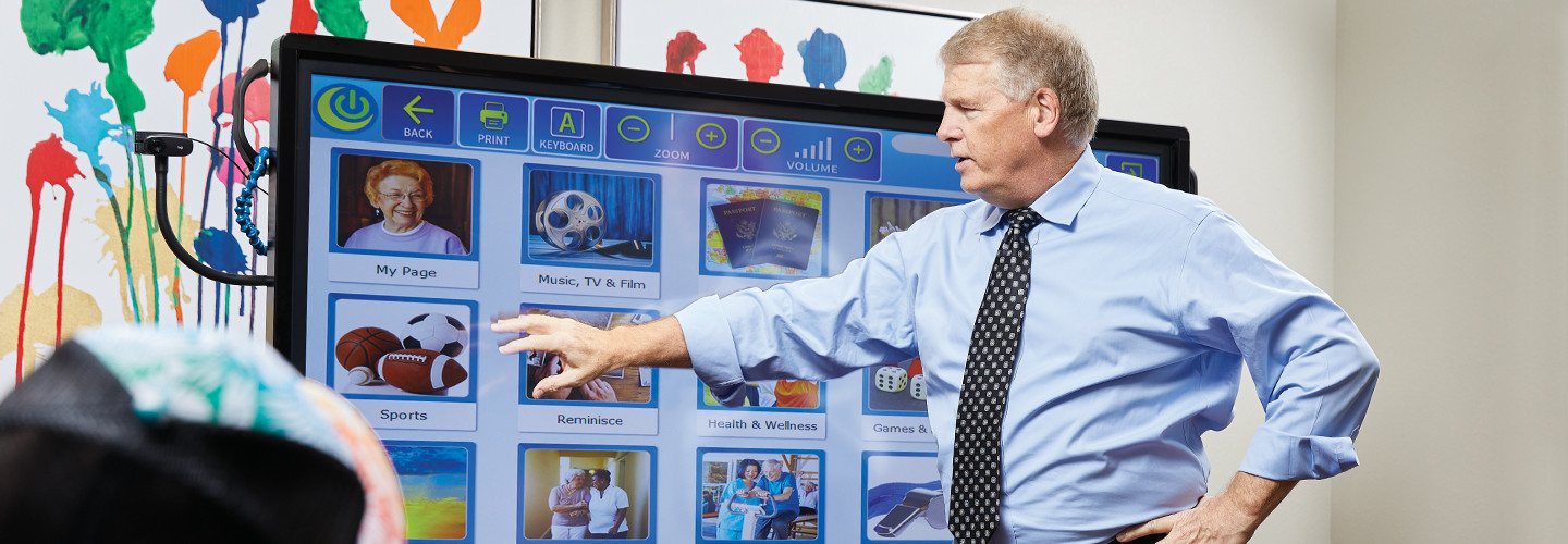 Chip Burns, CIO of Sun Health Communities, demonstrates interactive touch-screen technology that facilitates brain games, exercise routines and video chat, among other capabilities.