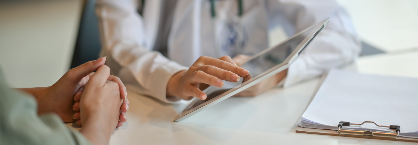 Doctor uses tablet to show patient data