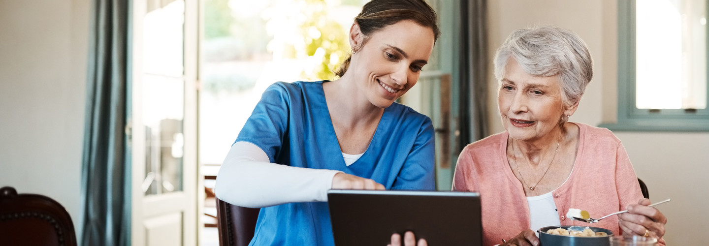 nurse and older adult with tablet
