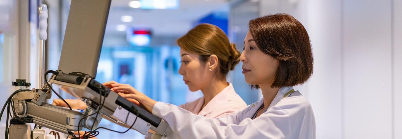 Doctor types at mobile EHR workstation