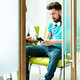 Young man sitting in waiting room at dental clinic using mobile phone