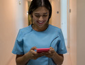 Latin american nurse walking through the hospital's corridor chatting on her smartphone smiling very happy