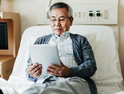 Man Reading on iPad in Hospital Room