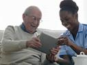 Happy senior man and home nurse sitting on sofa using digital tablet - Indoors