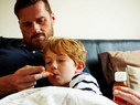Father measuring temperature of his sick son, while lying on bed