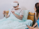 Nurse sitting by patient using VR headset