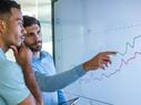 Businessman explaining line graph to his coworker.