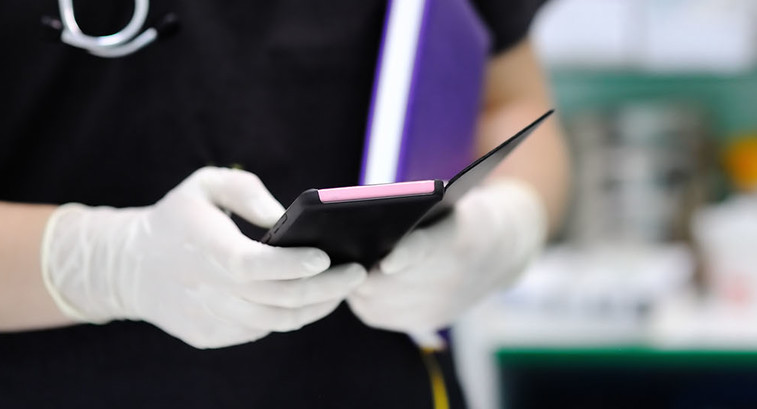 Nurse holding purple smartphone