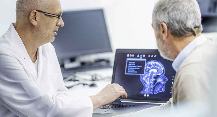 Doctor showing patient his brain scans on a computer after a successful brain tumour surgery.