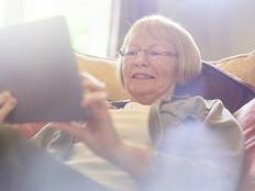 senior woman smiling as she uses her digital tablet
