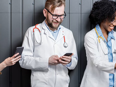 Multi ethnic group of medics standing with phones on the gray wall background