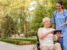 An old man sitting in a wheelchair shows the nurse something on his tablet
