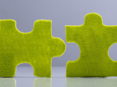 Side View Of Two Miniature Human Figures Solving Green Jigsaw Puzzles On Grey Background