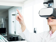 Horizontal color image of female dentist using virtual reality simulator at modern clinic.