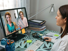Doctor at desk speaking with patient through video conference.