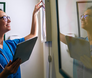 Side view of smiling middle aged nurse checking X-ray in a doctors office.