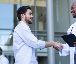 Doctor and patient shaking hands of hospital